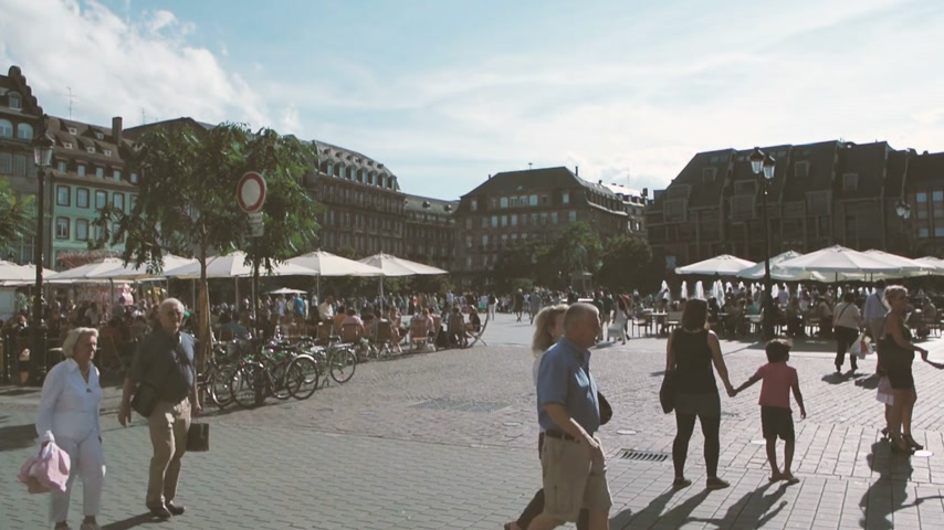 europe population : STRASBOURG, FRANCE - CIRCA 2016: Film view of Place Kleber in French city of Strasbourg on a summer day with pedestrian, travelers people walking on summer tour city Stock Footage
