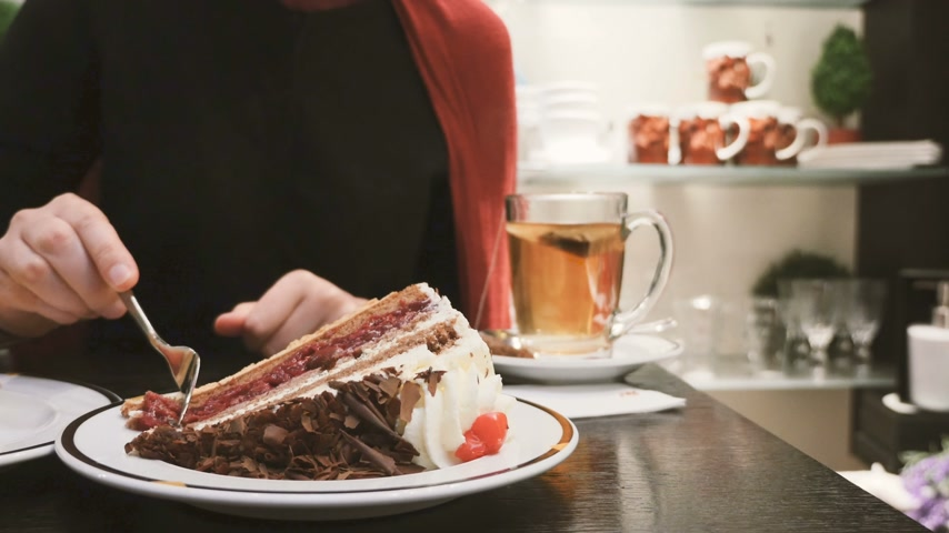 desszertek : Woman eating Black Forest gateau (British English) and Black Forest cake (American English and Australian English) are the English names for the German dessert Schwartzwalder Kirschtorte Stock mozgókép