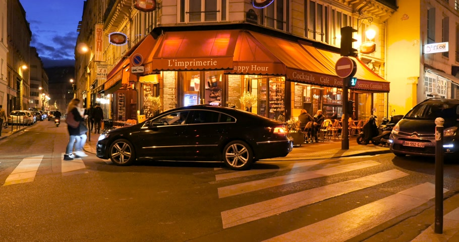architektura : PARIS, FRANCE - CIRCA 2016: Luxury Paris - lImprimerie cafe with luxury car parked with schafeur prive waiting for his clients in the heart of Paris at night with people enjoying coffee and having dinner