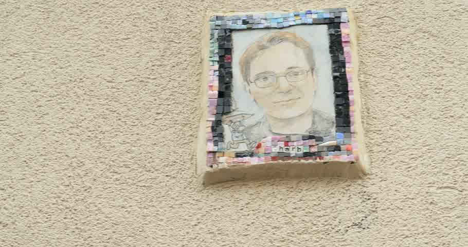 admirado : PARIS, FRANCE - CIRCA 2016: Charb  cartoonist and comic writer monument memorial on walls admired by pedestrian. Stephane Charbonnier (known by the pen-name Honore, was a French cartoonist and a long-time staff member of Charlie Hebdo. Stock Footage