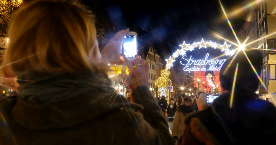 alsatian : STRASBOURG, FRANCE - CIRCA 2016: Neon lights above welcome gate entrance to with Christmas Capital signage with woman taking photos on mobile phone. In 2016 Christmas Capital is declared Strasbourg - one of the oldest Christmas markets in the world