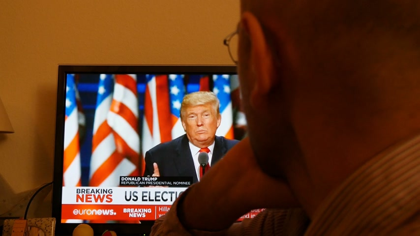 donald trump : PARIS, FRANCE - NOV 9, 2016: Man watching TV breaking news after US President Elections as Donald Trump is the 45th President of United States of America Stock Footage