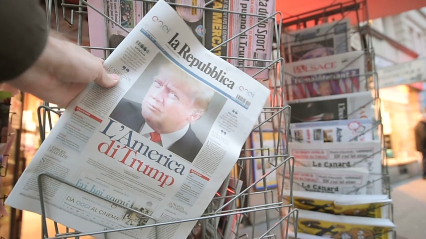 donald trump : PARIS, FRANCE - NOV 10, 2016: Man buying Italian newspaper La Republica with shocking headline title at press kiosk about the US President Elections - Donald Trump is the 45th President of United States of America
