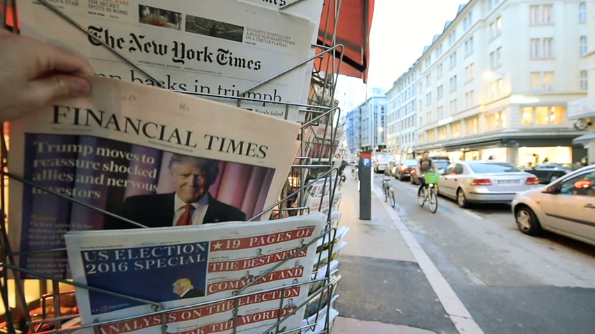 donald trump : PARIS, FRANCE - NOV 10, 2016: Man buying Financial Times newspaper with shocking headline title at press kiosk about the US President Elections - Donald Trump is the 45th President of United States of America