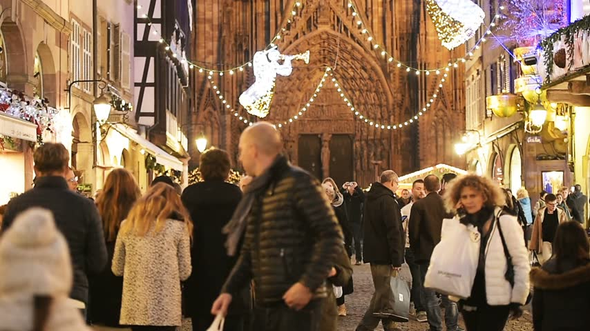 admirado : STRASBOURG, FRANCE - CIRCA 2016: Christmas Market atmosphere and Notre-Dame Cathedral admired by tourists pedestrians and locals on Rue Merciere