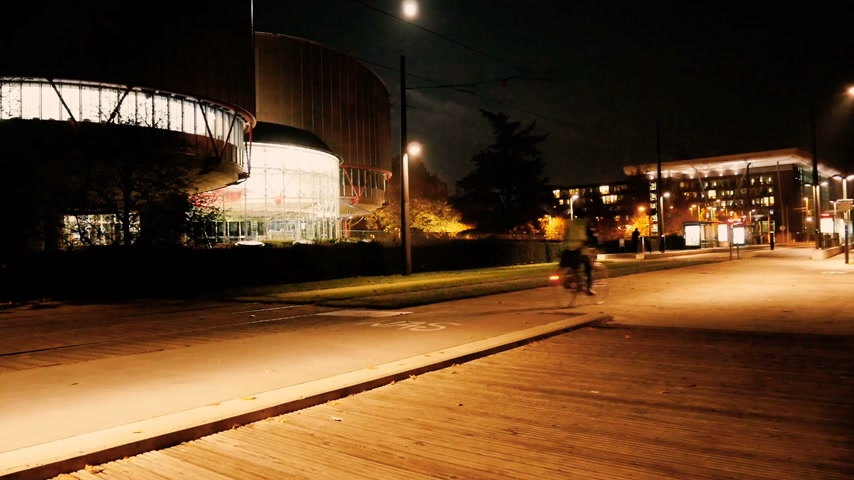 eljárás : STRASBOURG, France - CIRCA 2015: Established shot of European Court of Human Rights in Strasbourg at night with runners and cyclists Stock mozgókép