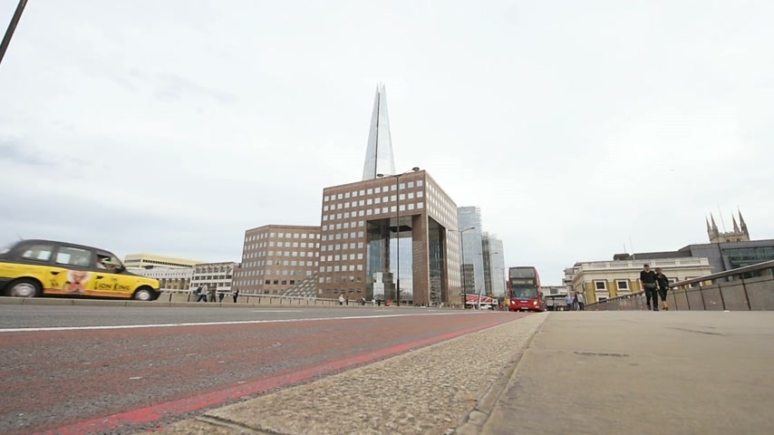 hackney carriage : London, United Kingdom - Circa 2016: Double-decker bus driving over London Bridge with the Shard skyscraper in the background Stock Footage