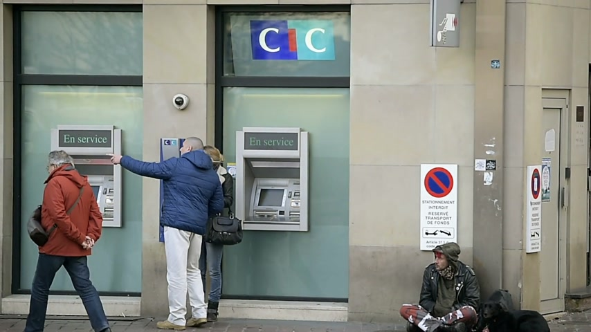 unlucky : STRASBOURG, FRANCE - CIRCA 2016:  Homeless beggar man begging for money and food near atm automatic teller machine in France with pedestrians passing indifferently near him