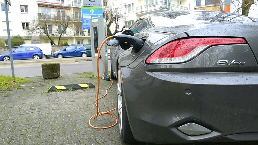 recharging : PARIS, FRANCE - CIRCA 2016: Rear view of an fast FISKER Karma electric car charging at Electric Charging Point in urban environment. Fisker Automotive, Inc. was an automaker originally from California.