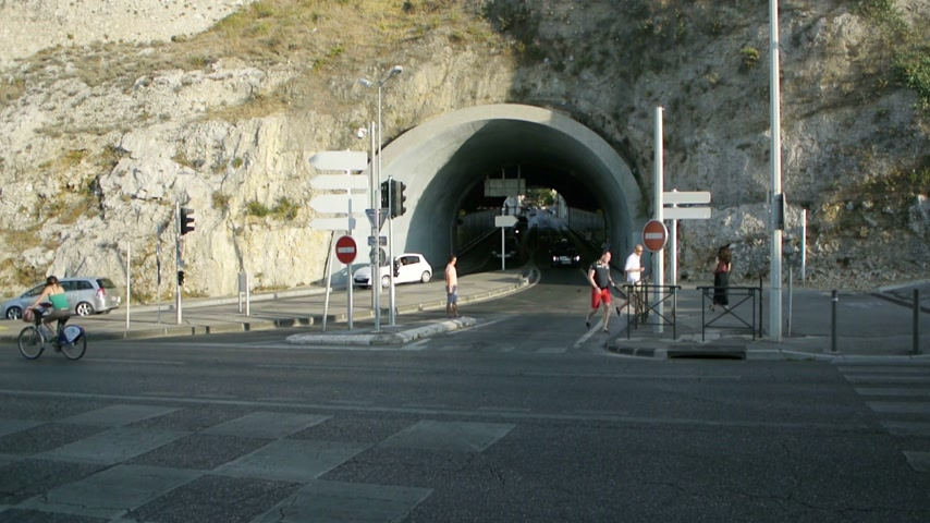 marseille : MARSEILLE, FRANCE - CIRCA 2015: Busy tunnel exit with cars driving and pedestrians at crossroads on a hot summer day in South of France