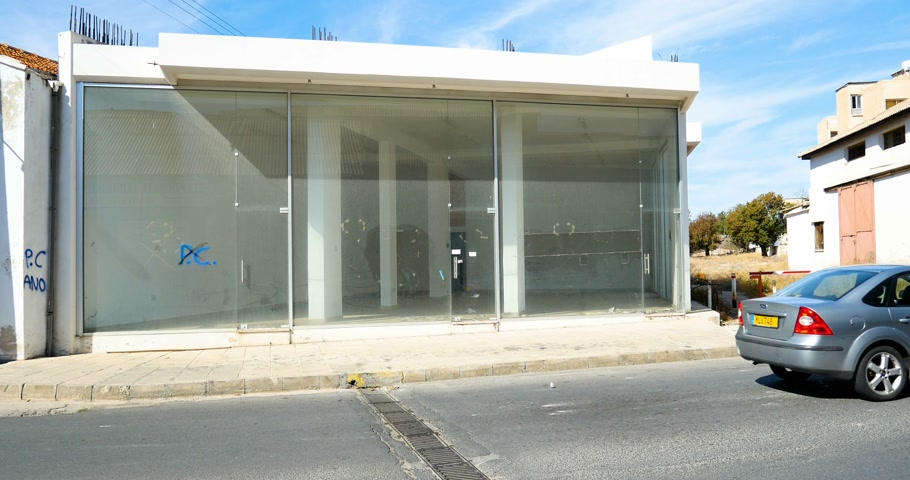 evacuated : PAPHOS, CYPRUS - CIRCA 2016, Modern store office building with glass facade and empty interior - moving in or moving out - on the sunny street of Paphos in Cyprus with cars driving Stock Footage