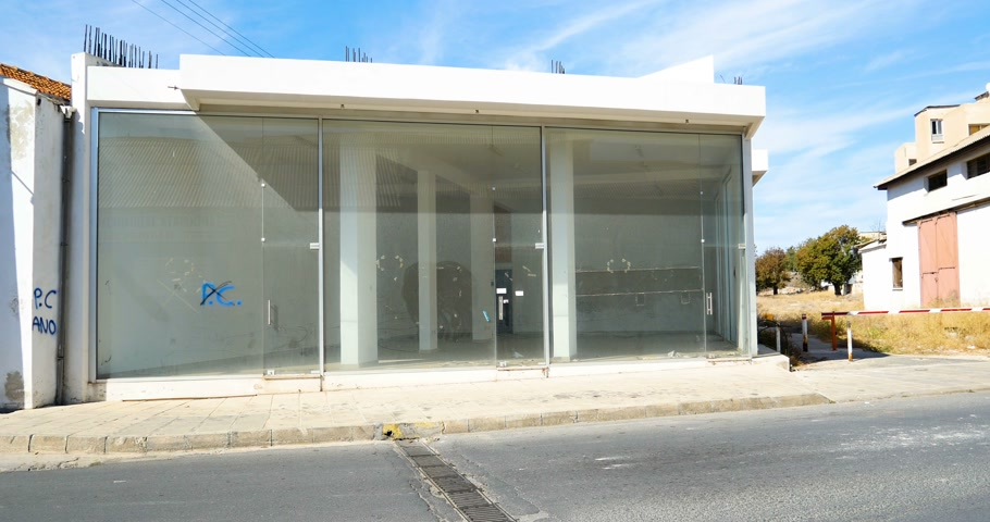 evacuated : PAPHOS, CYPRUS - CIRCA 2016, Store office building with glass facade and empty interior - moving in or moving out - on the sunny street of Paphos in Cyprus with cars driving Stock Footage