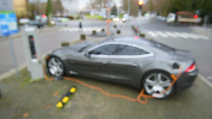 recharging : Aerial view of defocused electric car charging at Electric Charging Point in urban environment.