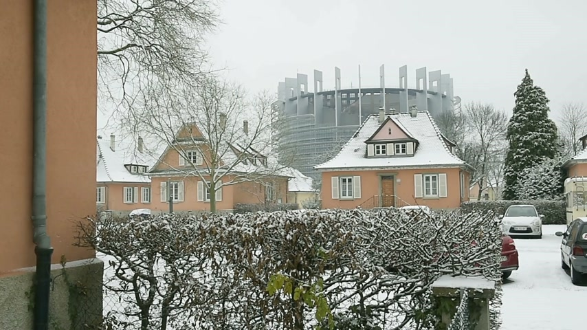 european court of human rights : STRASBOURG, FRANCE - CIRCA 2017: Snow falling on Strasbourg with view through houses of the European Parliament building on a cold winter day