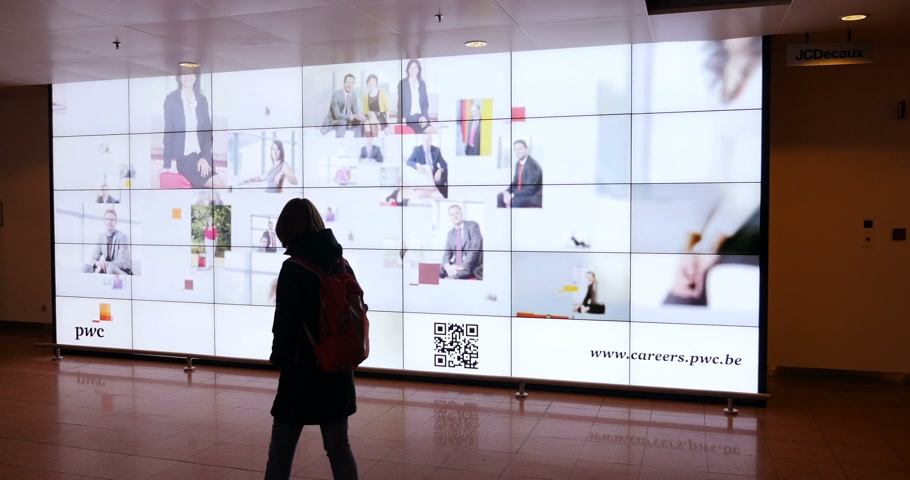 auditing : BRUSSELS, BELGIUM -  CIRCA 2016: Woman wearing backpack looking at the impressive gigantic LCD advertising banner about changing career and work for PWC PriceWaterHouse Are you Creative  Audit Stock Footage