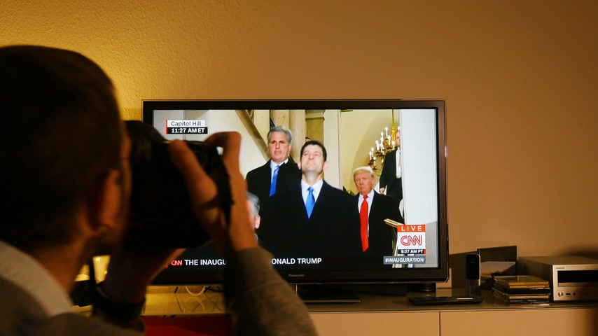 donald trump : PARIS, FRANCE - JAN 20, 2017 Man  watching TV taking photo news reporting 45th U.S. President Donald Trumps inauguration ceremony - arrival of Donald Trump and his team