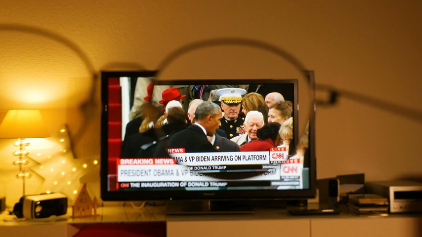 into focus : PARIS, FRANCE - JAN 20, 2017 Man  watching TV news reporting 45th U.S. President Donald Trumps inauguration ceremony - Barack Obama, Michele VP Biden shaking hands with Trump family seen through eyeglasses