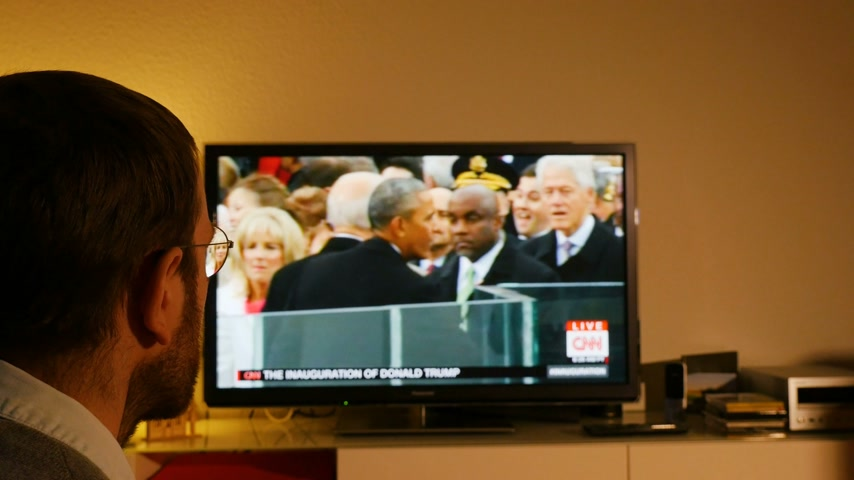 into focus : PARIS, FRANCE - JAN 20, 2017 Man  watching TV news reporting 45th U.S. President Donald Trumps inauguration ceremony - Barack Obama, shaking hands with former US president