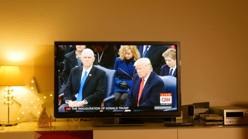 choral : PARIS, FRANCE - JAN 20, 2017 Man  listening watching TV news reporting 45th U.S. President Donald Trumps inauguration ceremony - Trump listens to Missouri State University Choral sings Now we belong: