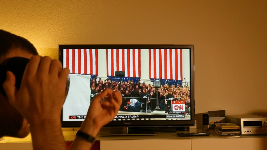 choral : PARIS, FRANCE - JAN 20, 2017 Man  wearing VR mask watching TV news reporting 45th U.S. President Donald Trumps inauguration ceremony - Missouri State University Choral sings Now we belong