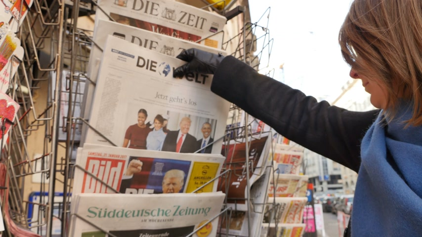 donald trump : PARIS, FRANCE - JAN 21, 2017: Woman purchases a Die Zeit German newspaper from a newsstand featuring photos and headlines with Donald Trump and Barack Obama inauguration as the 45th President of the United States in Washington, D.C Stock Footage