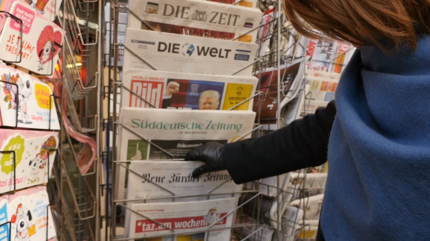 donald trump : PARIS, FRANCE - JAN 21, 2017: Woman purchases a German newspaper from a newsstand featuring headlines with Die Trump Show of Donald Trump inauguration as the 45th President of the United States in Washington, D.C