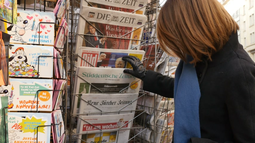donald trump : PARIS, FRANCE - JAN 21, 2017: Woman purchases reading German Dutch French from a newsstand featuring headlines with Die Trump Show of Donald Trump inauguration as the 45th President of the United States in Washington, D.C