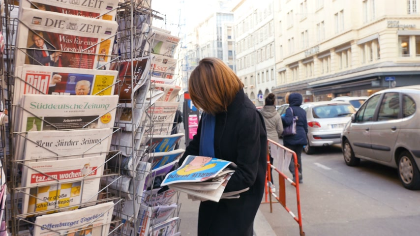 donald trump : PARIS, FRANCE - JAN 21, 2017: Woman purchases Un Doigt (A Finger) French newspaper from a newsstand featuring headlines with Donald Trump inauguration as the 45th President of the United States in Washington, D.C