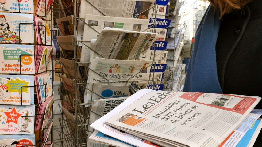 usa today : PARIS, FRANCE - JAN 21, 2017: Woman purchases a USA TODAY newspaper from a newsstand featuring headlines with Donald Trump inauguration as the 45th President of the United States in Washington, D.C