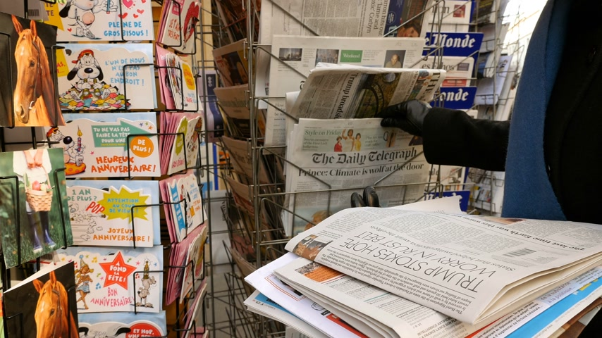 donald trump : PARIS, FRANCE - JAN 21, 2017: Woman purchases The Daily Telegraph newspaper from a newsstand featuring headlines with Donald Trump inauguration as the 45th President of the United States in Washington, D.C