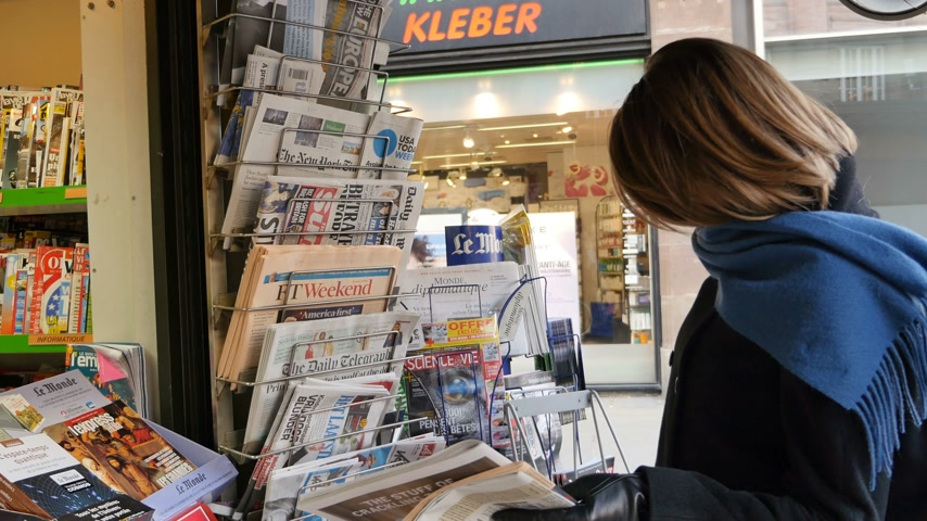 donald trump : PARIS, FRANCE - JAN 21, 2017: Woman purchases a The Wall Street Journal US newspaper from a newsstand featuring headlines with Donald Trump inauguration as the 45th President of the United States in Washington, D.C Stock Footage