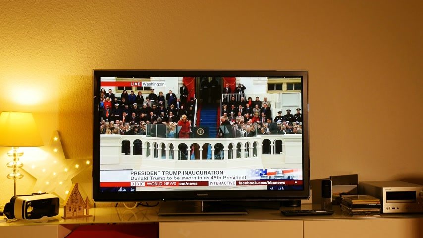 evangelical : PARIS, FRANCE - JAN 20, 2017 Man  watching TV taking photo news reporting 45th U.S. President Donald Trumps inauguration ceremony - Sam Rodriguez Latino pastor speech before inauguration