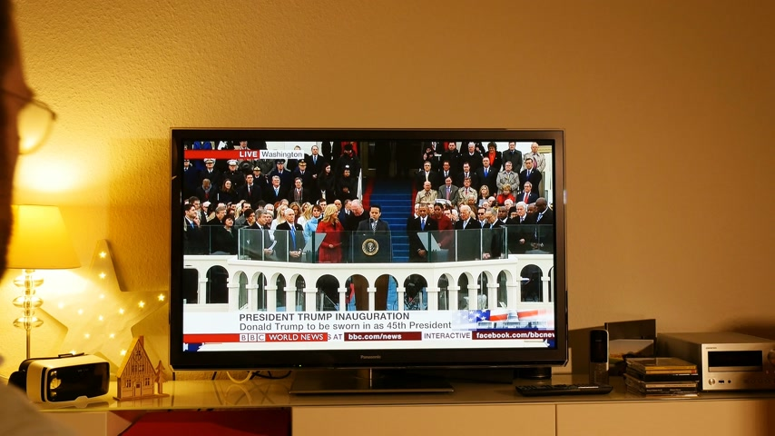 evangelical : PARIS, FRANCE - JAN 20, 2017 Man  watching praying TV taking photo news reporting 45th U.S. President Donald Trumps inauguration ceremony - Sam Rodriguez Latino pastor speech before inauguration