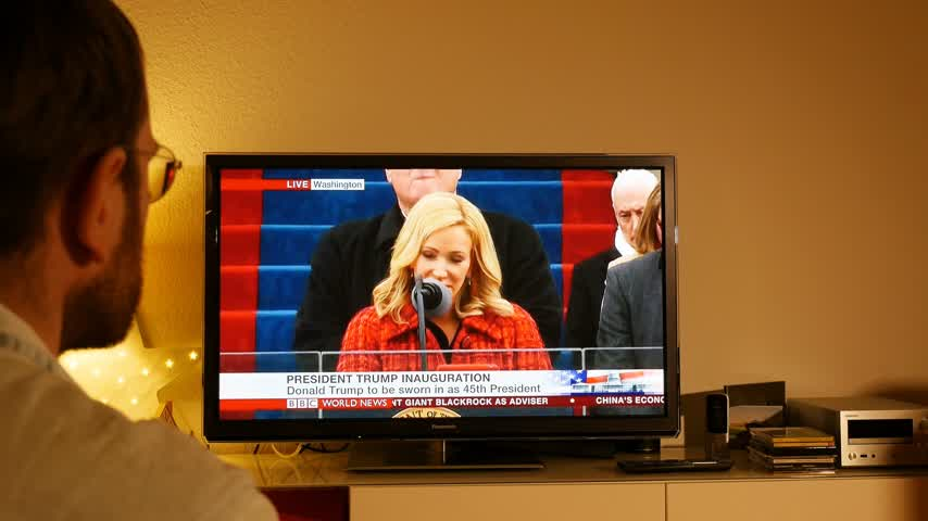 allegiance : PARIS, FRANCE - JAN 20, 2017 Man watching TV news reporting 45th U.S. President Donald Trumps inauguration ceremony - pledge of allegiance by Pastor Paula White, New Destiny Christian Center Stock Footage