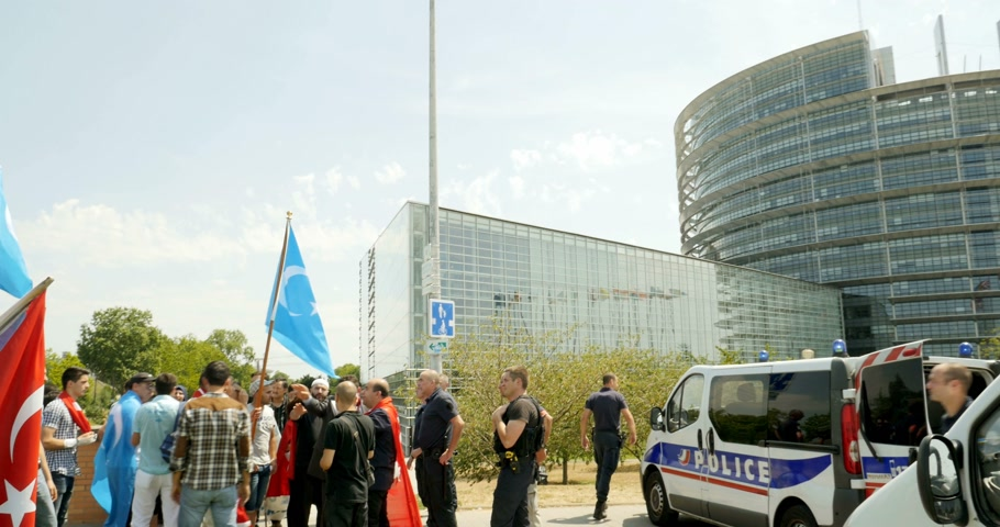 sürgün : STRASBOURG, FRANCE - CIRCA 2015: Uyghur human rights activists surveilled by police fore at the demonstration at the European Parliament to protest against Chinese governments policy in Uyghur