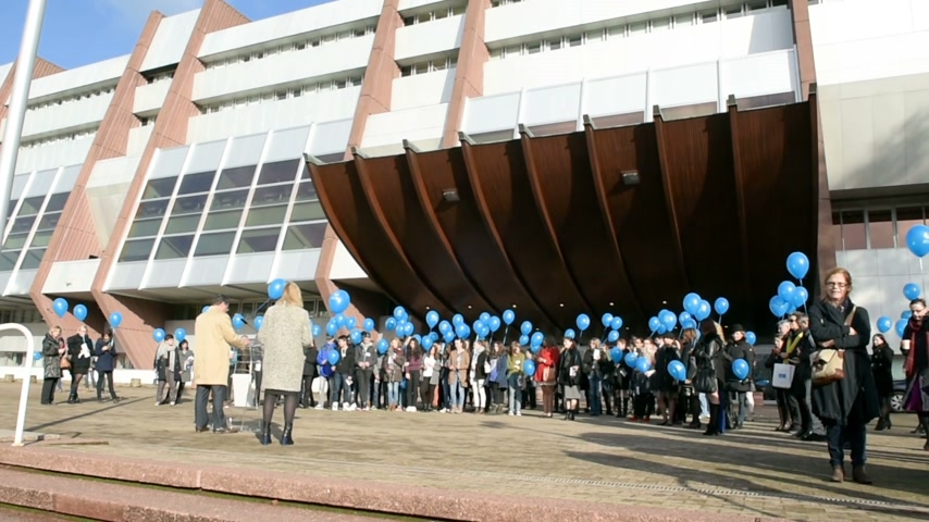 coe : STRASBOURG, FRANCE - DEC 09, 2015: COE employees and kids celebrating the first European Day on the Protection of Children against Sexual Exploitation and Sexual Abuse by launching blue balloons Stock Footage