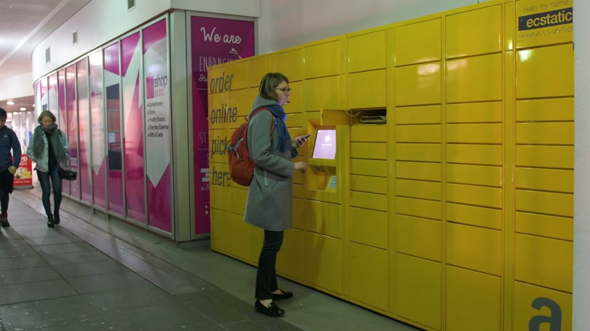 paket : LONDON, UNITED KINGDOM - CIRCA 2017: Woman taking parcel from the Amazon locker orange delivery package locker in the University Campus - Amazon Locker self-service parcel delivery service offered by online retailer Amazon.com.
