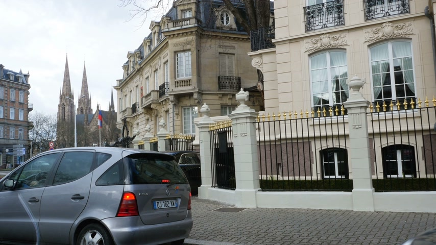 groupe : STRASBOURG, FRANCE - CIRCA 2017: Waving Russian Federation flag waving in front of Consulate of Russia in Strasbourg, France With nearby luxury house and Rolls-Royce car parked in front of it Stock Footage