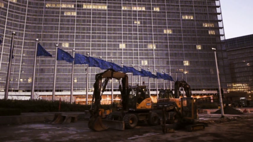 funcionários : BRUSSELS, BELGIUM - CIRCA 2016: Vintage 16 mm effect over Flags of European Union in front of the office windows of the Berlaymont building of the European Commission in Brussels, Belgium at dusk - wide lens newsworthy style