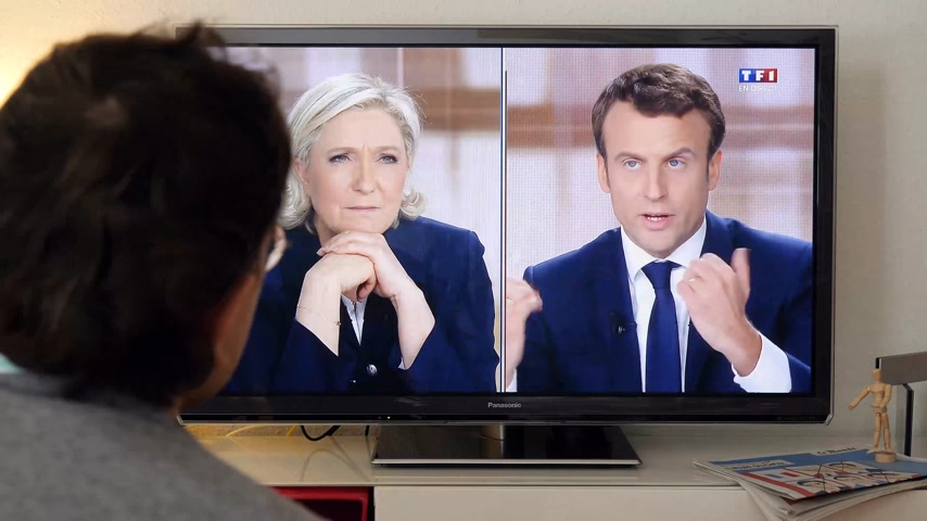 human interest : PARIS, FRANCE - MAY 03, 2017: Supporter of President watch E Macron at the TV talking addressing to Le Pen about returning to Franc- debate between Emmanuel Macron and Marine Le Pen on a home TV