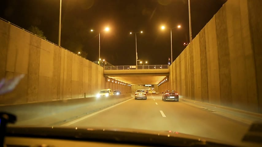 traffic bucharest : BUCHAREST, ROMANIA - CIRCA 2016: Driver point of view personal perspective driving at night in Bucharest neighborhood, entering exit tunnel