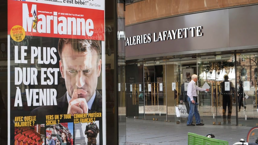 lafayette : STRASBOURG, FRANCE - MAY 15, 2017: Press Kiosk advertising with Emmanuel Macron image and text - the hard time will come soon - after handover ceremony presidential inauguration of the newly elected French President Emmanuel Macron galeries lafayette,