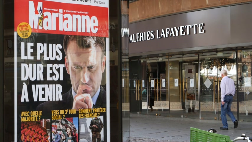 dur : STRASBOURG, FRANCE - MAY 15, 2017: Press Kiosk advertising with Emmanuel Macron image and text - the hard time will come soon - after handover ceremony presidential inauguration of the newly elected French President Emmanuel Macron galeries lafayette,