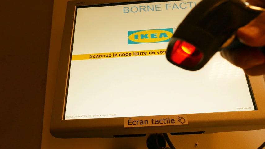 számla : PARIS, FRANCE - CIRCA 2017: Male customer using the barcode scanner to scan the ticket and receive the invoice inside the IKEA furniture store
