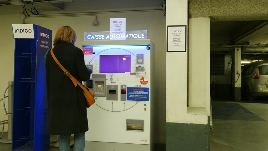 vending machine : PARIS, FRANCE - CIRCA 2017: Woman paying for the underground parking at the touchscreen parking meter Stock Footage