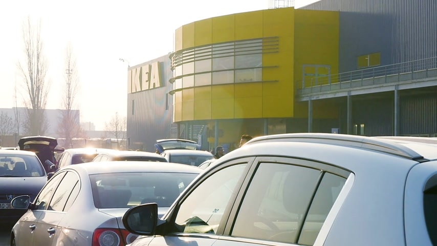 motorcar : PARIS, FRANCE - CIRCA 2017: People walking between multiple parked cars in the IKEA parking with the furniture store in the background Stock Footage
