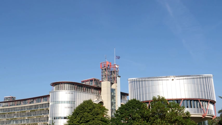 coe : Zoom-out from European Union flag fly half-mast European Court of human Rights building memory of victims terrorist explosion Manchester Arena