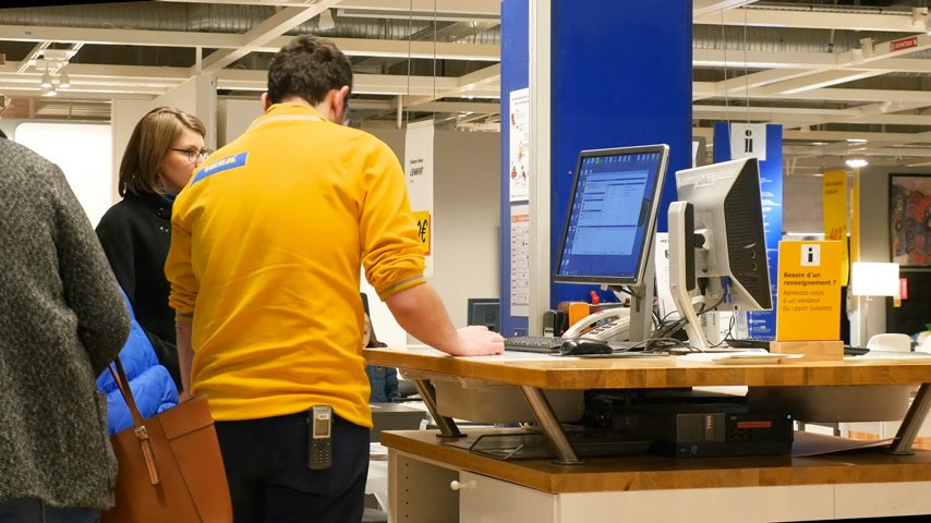 kitchen furniture : PARIS, FRANCE - CIRCA 2017: Young beautiful woman being helped by IKEA staff member to find the right product code in the online computer database - printing invoice