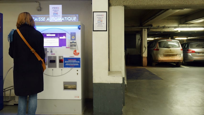 vending machine : PARIS, FRANCE - CIRCA 2017: Car driving near woman paying for the underground parking at the touchscreen parking meter Stock Footage