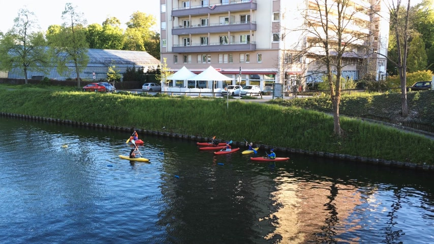 kenu : STRASBOURG, FRANCE - CIRCA 2017: group of kids kayaking on Ill river in Strasbourg in front of Francesca restaurant and a few meter from European Parliament and ECHR